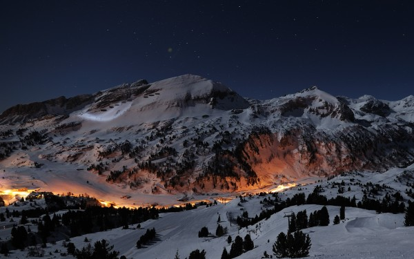 House-with-Lights-Under-Snowy-Mountains