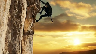 Man-Climning-Mountain-at-Sunset