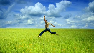 Man-Jumps-in-Green-Field-Against-Blue-Sky