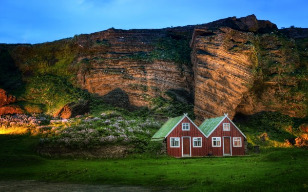 Wooden-Houses-Under-Mountain-Cliff