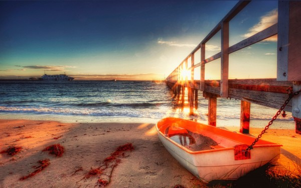 small_boat_on_the_beach_sand-wide